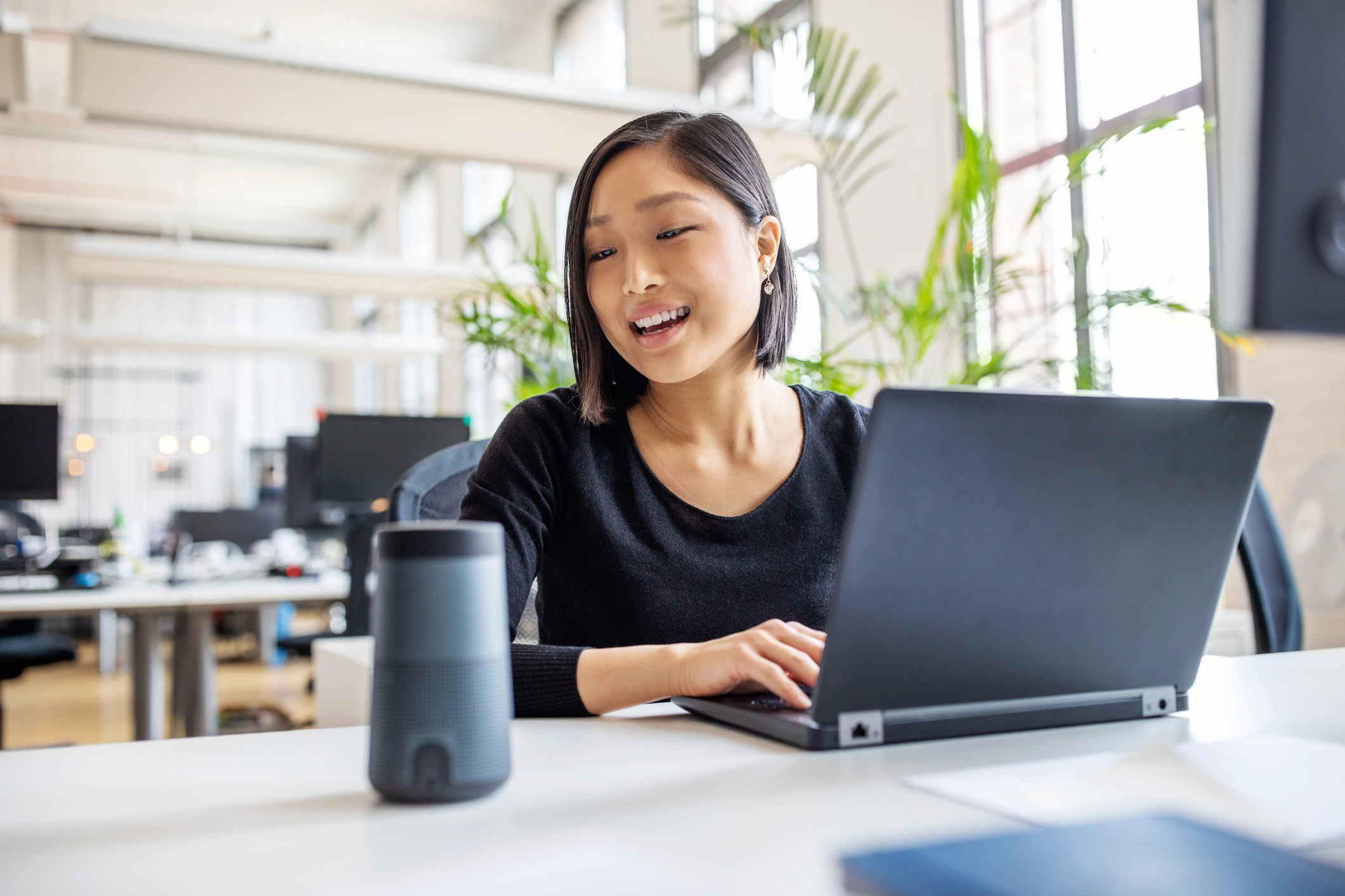 Female professional using virtual assistant at desk